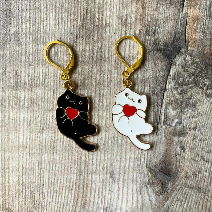 Set of two progress keepers for knitting or crochet, cats holding hearts, one white, one black